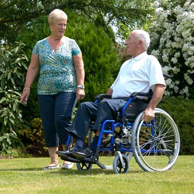 man in wheelchair on a lawn with woman, chatting